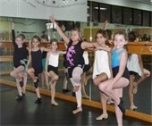 Six young girls in dance attire and dance poses