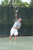 Man jumping to hit a tennis ball on a tennis court