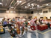 Vendor craft booths set up in the gymnasium with people shopping