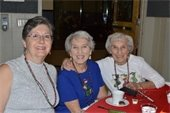 Three ladies wearing holiday beads at the Holiday Luncheon