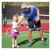 Male instructor teaching a young girl how to hold a tennis racket.