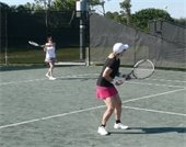 Two women playing tennis at the PBG Tennis Center
