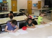 Six boys and girls drawing pictures in art class