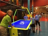 A camp counselor and 3 kids standing at an air hockey table.