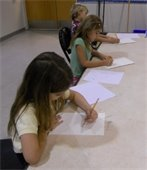 Two girls and a boy drawing in art class.