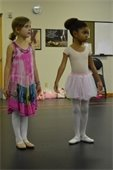 Two girls standing in ballet attire