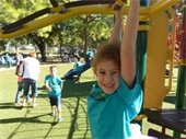 Little girl hanging on playground equipment