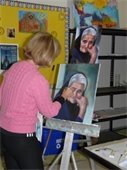 A woman painting a portrait of an elderly lady