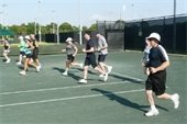 Men and women running on the tennis court during Cardio Tennis