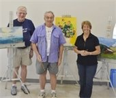 Three male and female art students displaying their artwork.