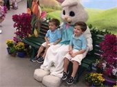 Two little boys sitting on either side of the Bunny on a bench