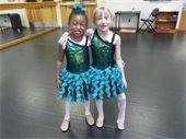 One little girl with her arm around another little girl, both in dance costumes