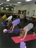 One man and three women in a yoga position