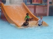 Three young children sliding down a water slide