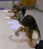 Two girls and a boy drawing on paper in art class