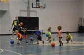 Young boys and girls learning basic basketball skills