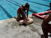 A female lifeguard practicing CPR on a mannequin