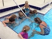 A female instructor teaching young children swimming lessons