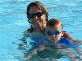 A female swim instructor giving swim lessons to a young boy