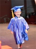 A young boy smiling in his cap and gown for PreK Graduation