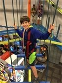 A boy in a harness on an indoor high ropes course