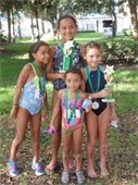 Four girls wearing medals and holding trophies