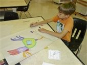 A boy drawing a picture with pastels