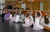 Little ballerinas at the barre with their teacher
