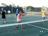 Men and women participating in a tennis fitness class