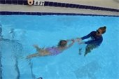 A little girl swimming under water to her instructor