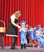 A young boy in cap and gown receiving his Pre-K diploma
