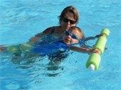 A female instructor teaching a little boy swim lessons