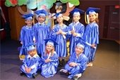 Eight young boys and girls wearing graduation caps and gowns holding diplomas