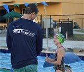 A male lifeguard in MedExpress shirt and young girl in swimsuit and cap standing at the pool