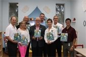 "City officials holding the book ""Quackers"" by Liz Wong"