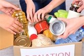 Hands putting food items in a box