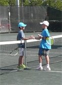 Two boys shaking hands over a tennis net