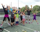 A group of kids on a tennis court jumping up with their hands in the air