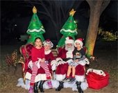 A girls and boy sitting on Santa and Mrs. Claus' laps