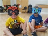 Two young boys wearing bug masks