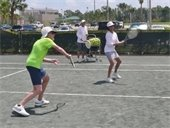 A man and woman in the Hitting Frenzy class with the instructor in the background