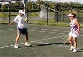 A male instructor teaching a female student tennis technique