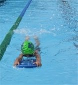 A young child swimming laps with a kickboard in a pool