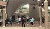 A group of adults doing Tai Chi on the plaza