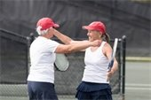 Two female tennis players smiling and getting ready to hug
