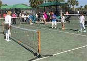 Special needs tennis players on the court with an instructor