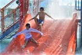 A boy and a girl sliding down a water slide