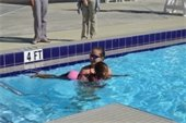 A young girl in the pool with a swim instructor