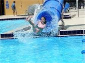 A girl sliding out of an enclosed water slide