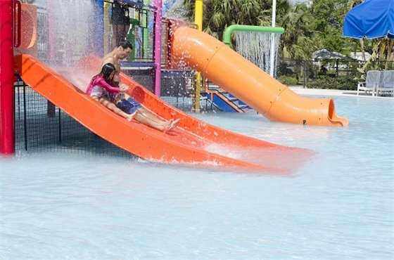 A dad and daughter sliding down a water slide